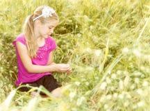 Ein Mädchen, das draußen sitzt stockbild