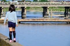 Ein Mädchen, das durch Fluss von Arashiyama geht Lizenzfreie Stockfotografie