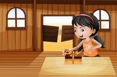 Ein Mädchen, das ein Geschenk über der Tabelle in der Saalstange auspackt Lizenzfreies Stockbild