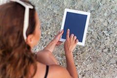 Ein Mädchen, das ein teblet in ihren Händen auf der Küste des Meeres nimmt Lizenzfreie Stockbilder
