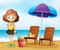 Ein Mädchen, das eine Eiscreme am Strand isst Stockfotografie