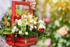 Ein Mädchen, das eine schöne Zusammensetzung von Blumen in ihren Händen hält lizenzfreies stockfoto