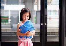 Ein Mädchen, das eine Schweinpuppe, tief im Gedanken hält lizenzfreie stockfotos