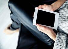 Ein Mädchen, das eine Tablette in den Händen, Leser mit einer netten Maniküre hält Lederne Hose, lizenzfreies stockbild