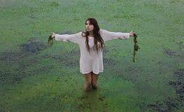 Ein Mädchen, das in einem Sumpf steht Stockfoto