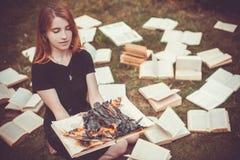 Ein Mädchen, das einen Buch Burning in der Natur im Sommergarten hält lizenzfreie stockfotografie