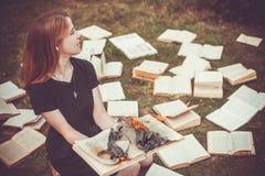 Ein Mädchen, das einen Buch Burning in der Natur im Sommergarten hält lizenzfreies stockbild
