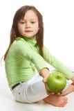Ein Mädchen, das einen grünen Apfel anbietet Lizenzfreies Stockbild
