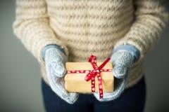 Ein Mädchen, das einen Kasten mit einem Weihnachtsgeschenk hält Stockfotos
