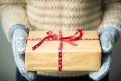 Ein Mädchen, das einen Kasten mit einem Weihnachtsgeschenk hält Stockfoto