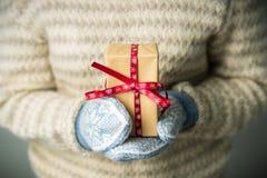Ein Mädchen, das einen Kasten mit einem Weihnachtsgeschenk hält Lizenzfreies Stockbild