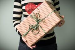 Ein Mädchen, das einen Kasten mit einem Weihnachtsgeschenk hält Lizenzfreie Stockbilder