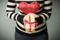 Ein Mädchen, das einen Kasten mit einem Weihnachtsgeschenk hält Lizenzfreie Stockfotografie