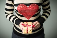 Ein Mädchen, das einen Kasten mit einem Weihnachtsgeschenk hält Lizenzfreies Stockfoto