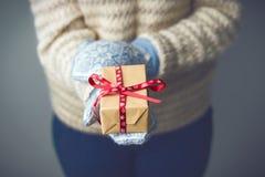 Ein Mädchen, das einen Kasten mit einem Weihnachtsgeschenk hält Stockfotografie