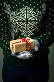 Ein Mädchen, das einen Kasten mit einem Weihnachtsgeschenk hält Lizenzfreie Stockfotos