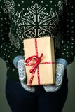 Ein Mädchen, das einen Kasten mit einem Weihnachtsgeschenk hält Stockbild