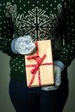 Ein Mädchen, das einen Kasten mit einem Weihnachtsgeschenk hält Stockbilder