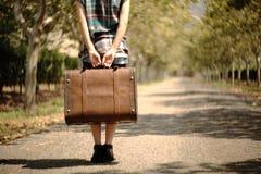 Ein Mädchen, das einen Koffer auf einer Bahn trägt Stockfotos
