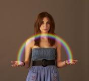 Ein Mädchen, das einen Regenbogen anhält Lizenzfreie Stockfotos