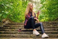 Ein Mädchen, das einen Smartphone verwendet und sitzt auf den Schritten Lizenzfreies Stockfoto