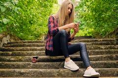 Ein Mädchen, das einen Smartphone verwendet und sitzt auf den Schritten Stockfotos