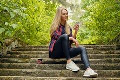 Ein Mädchen, das einen Smartphone verwendet und sitzt auf den Schritten Stockbild