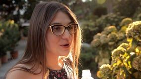 Ein Mädchen, das in einen Sommerpark geht, berührt eine ungewöhnliche schöne Anlage einer Blume stock footage