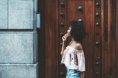 Ein Mädchen, das einen Wechselsprechanlagenknopf zurückruft stockfoto