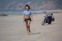 Ein Mädchen, das entlang einen wilden Strand von einem Motorrad geht Stockfoto