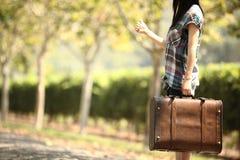 Ein Mädchen, das entlang einer Straße per Anhalter fährt Stockbild