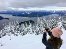 Ein Mädchen, das ein Foto auf Zypresse-Berg übersieht den Ozean unten macht stockfoto
