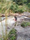Ein Mädchen, das Foto des Wasserfalls macht lizenzfreies stockfoto