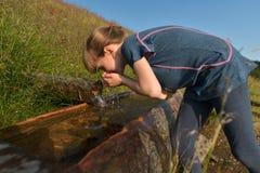 Ein Mädchen, das frisches Rohwasser vom Gebirgsfrühling trinkt Lizenzfreie Stockfotos