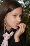 Ein Mädchen, das ihre Nägel in der Verzweiflung beißt Lizenzfreie Stockfotos