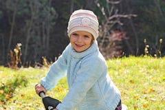 Ein Mädchen, das im Herbst spielt lizenzfreies stockfoto