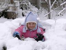 Ein Mädchen, das im Schnee liegt Stockbild