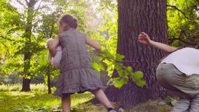 Ein Mädchen, das mit der Puppe im Park spielt stock footage