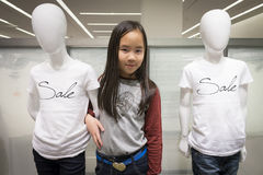 Ein Mädchen, das mit Modellen am Modeshop aufwirft Lizenzfreie Stockfotos
