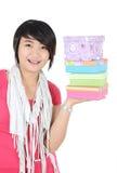 Ein Mädchen, das mit tragendem Stapel von Geschenken lächelt Lizenzfreie Stockfotos