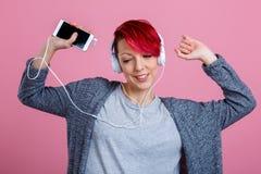 Ein Mädchen, das Musik auf Kopfhörern mit Telefon hört und mit ihren Händen oben tanzt Auf einem rosa Hintergrund stockfotografie