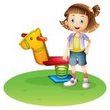 Ein Mädchen, das neben einem Pferdefrühlingsspielzeug steht lizenzfreie abbildung