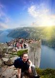 Ein Mädchen, das an in Norwegen-Bergen, mit Leuten auf einem Prediger ` s Kanzel-Felsen von einem Lysefjord stillsteht Lizenzfreie Stockfotos