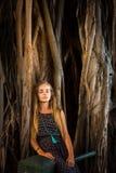 Ein Mädchen, das unter einem Banyanbaum stillsteht stockfoto