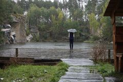 Ein Mädchen, das unter einem blauen Regenschirm steht und die Regentropfen auf dem Teich betrachtet lizenzfreie stockfotografie