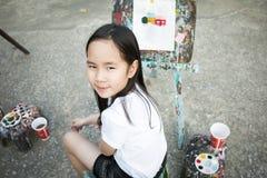 Ein Mädchen, das vor Gemälderahmen lächelt Stockbilder