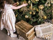 Ein Mädchen, das Weihnachtsbaum mit Glasweihnachtsbällen und -spielwaren verziert stockbilder