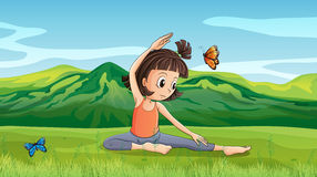Ein Mädchen, das Yoga nahe den Hügeln tut Lizenzfreies Stockfoto
