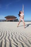 Ein Mädchen, das Yoga am Strand tut Lizenzfreie Stockfotos
