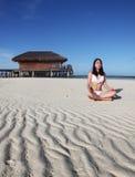 Ein Mädchen, das Yoga am Strand tut Lizenzfreies Stockfoto